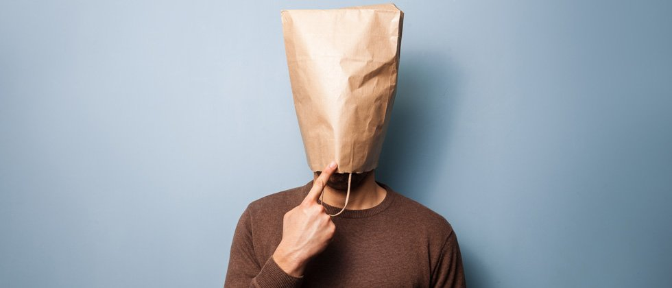 A man standing with a brown paper bag over his head