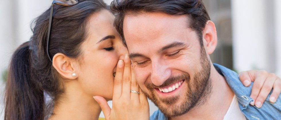 A woman whispering something into her date's ear making him laugh