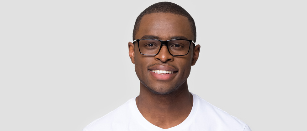 A young man in glasses smiling at the camera