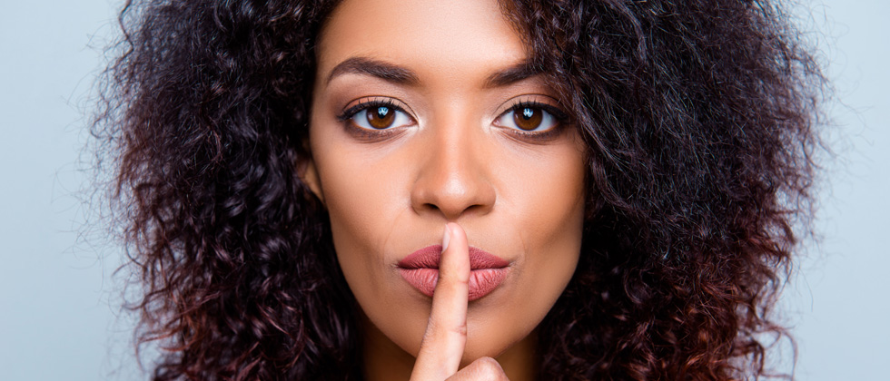 A woman with her finger over her lips as if to say be quiet