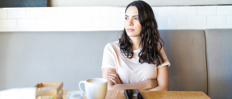 A woman at a café alone looking annoyed and staring into space