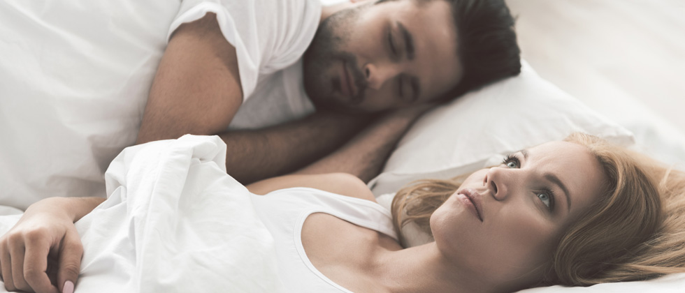 Couple in bed with the man sleeping and woman lying there thinking