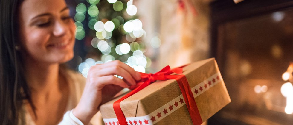 Woman happily opening a holiday gift next to the tree