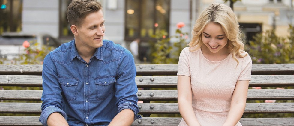 A young couple flirting on a park bench together