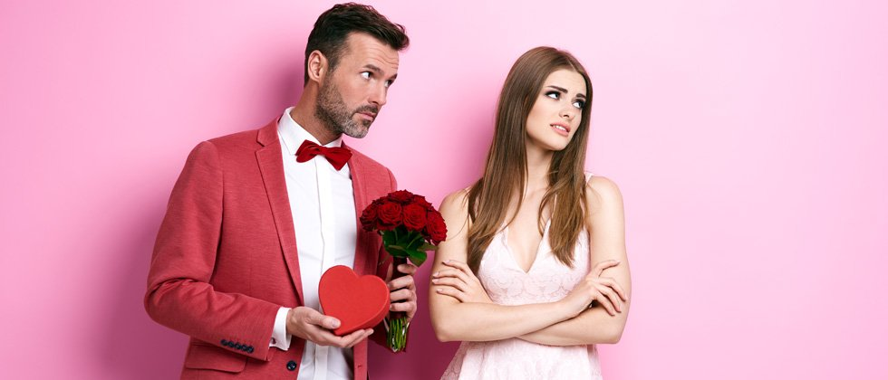 A couple against a pink wall looking annoyed holding flowers &candy