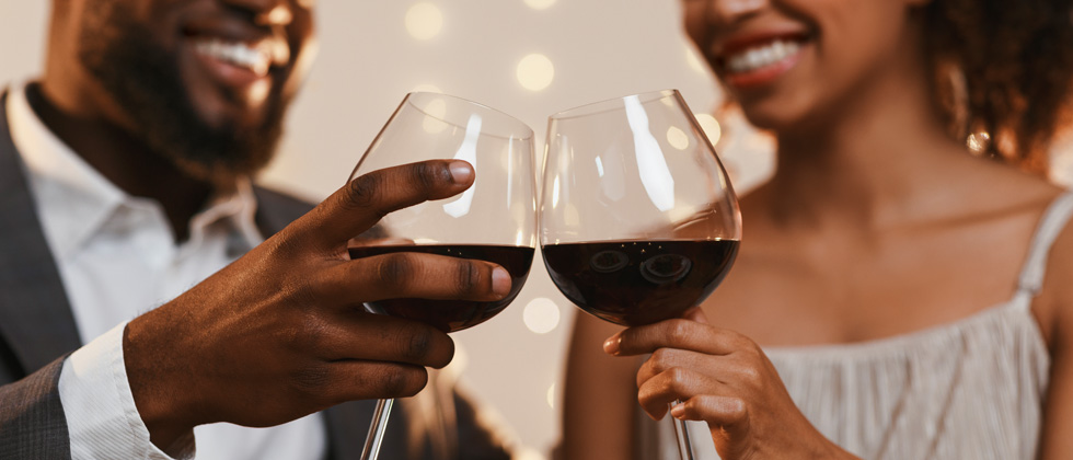 A couple cheering over red wine and smiles