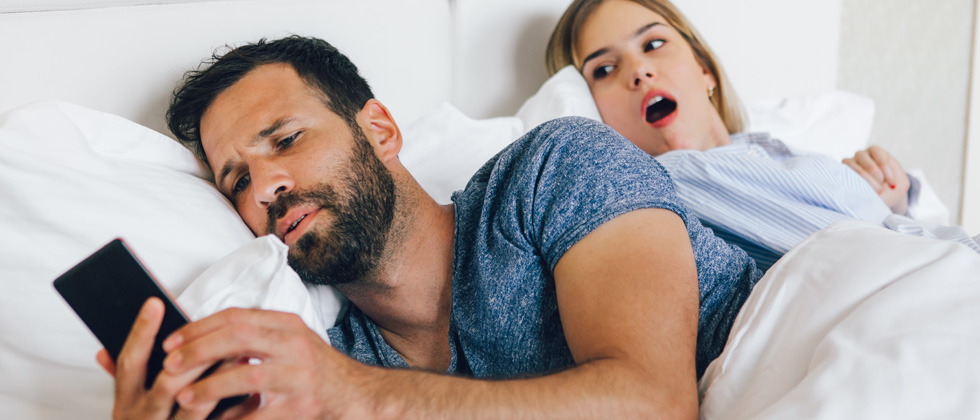 Couple in bed, one texting someone else and the other can see