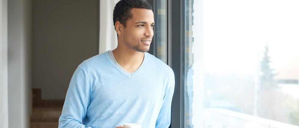A young guy staring out a window holding coffee and smiling