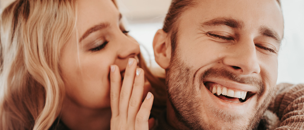 Woman whispering something flirty into her boyfriend's ear