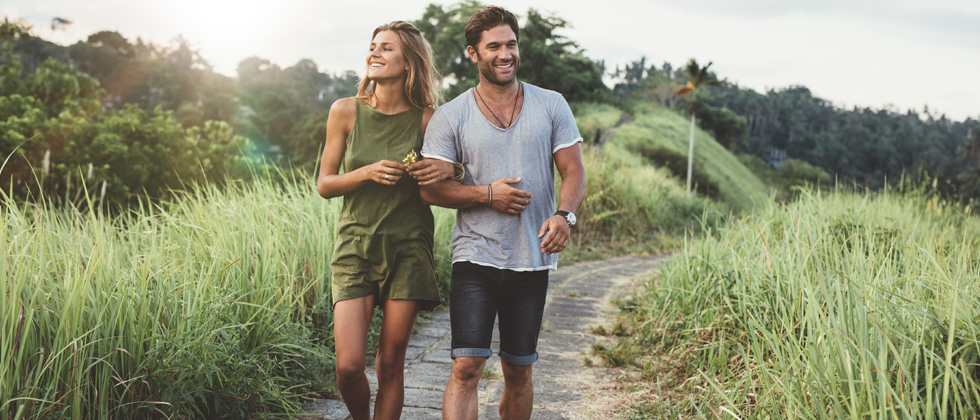 Couple walking along a scenic path while holding hands & smiling