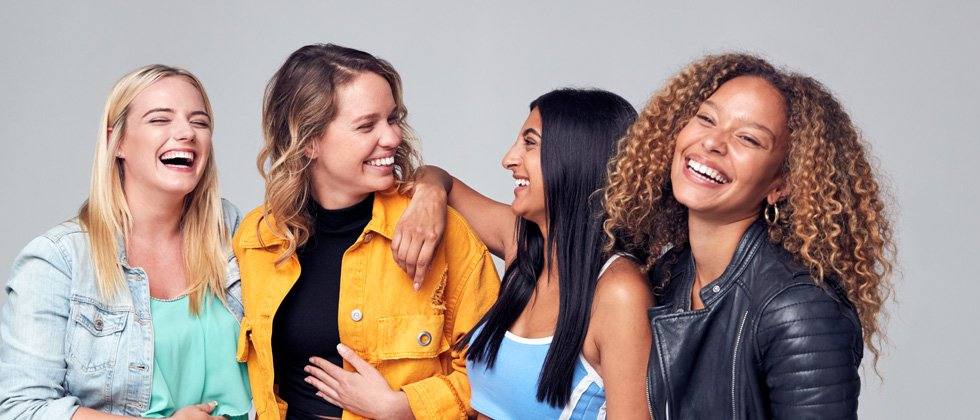 A group of young women standing laughing while standing close together