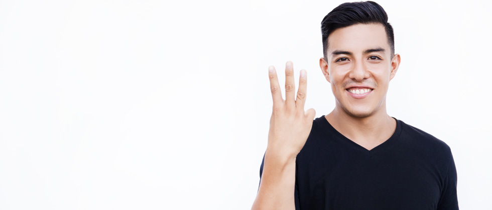 Young guy in a black shirt holding up 3 fingers