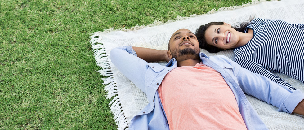 Interracial couple laying together on a picnic blanket in a field