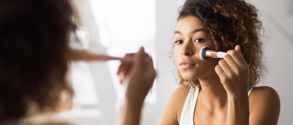 Young woman looking into the mirror while brushing on makeup