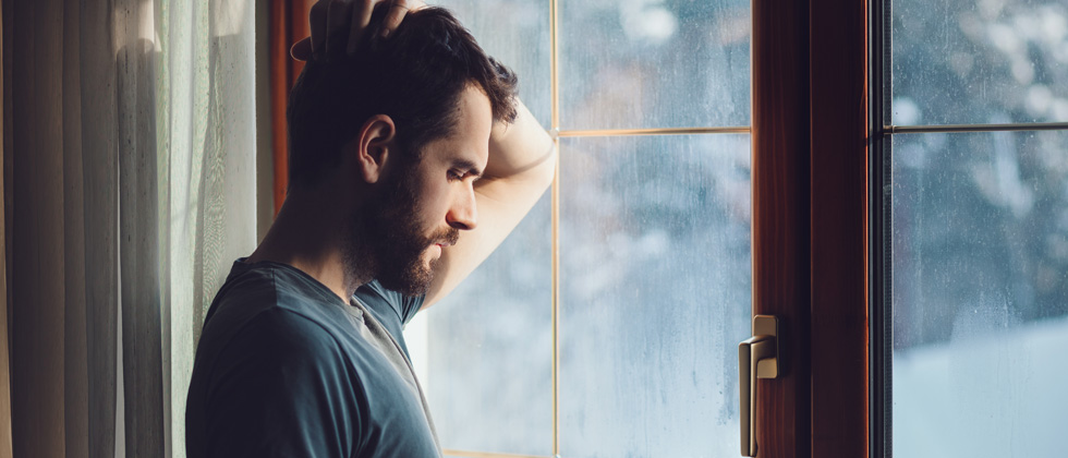 Man sadly looking out a rainy window in deep thought