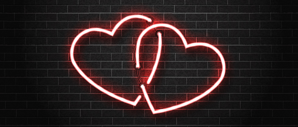 Two interlocked pink heart lights on a wall