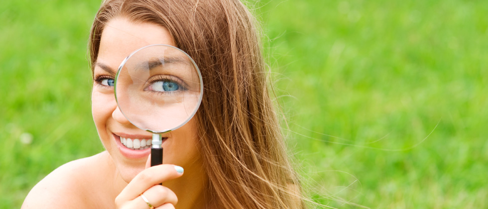 A woman holding a magnifying glass up to one eye
