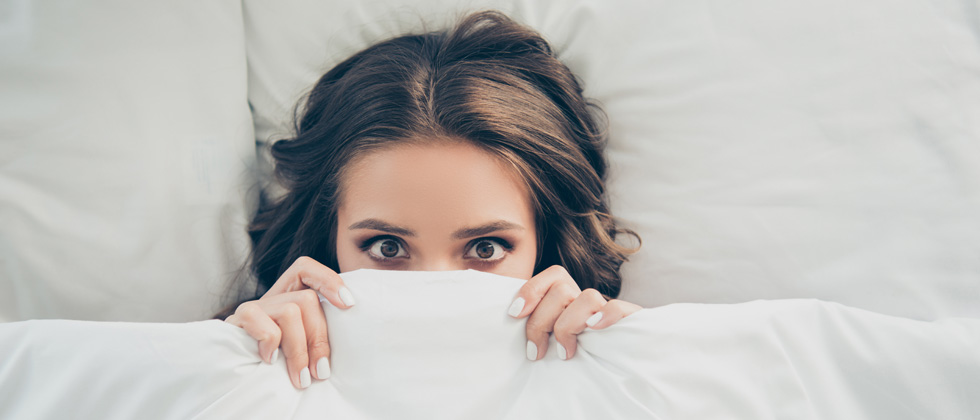 A woman in bed looking scared with the covers partly over her face