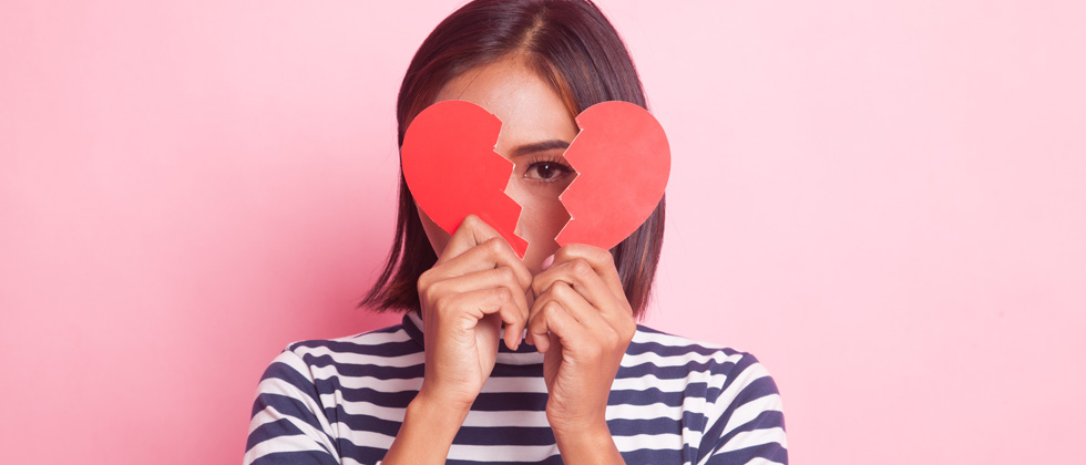 A woman holding a broken heart cutout over her face
