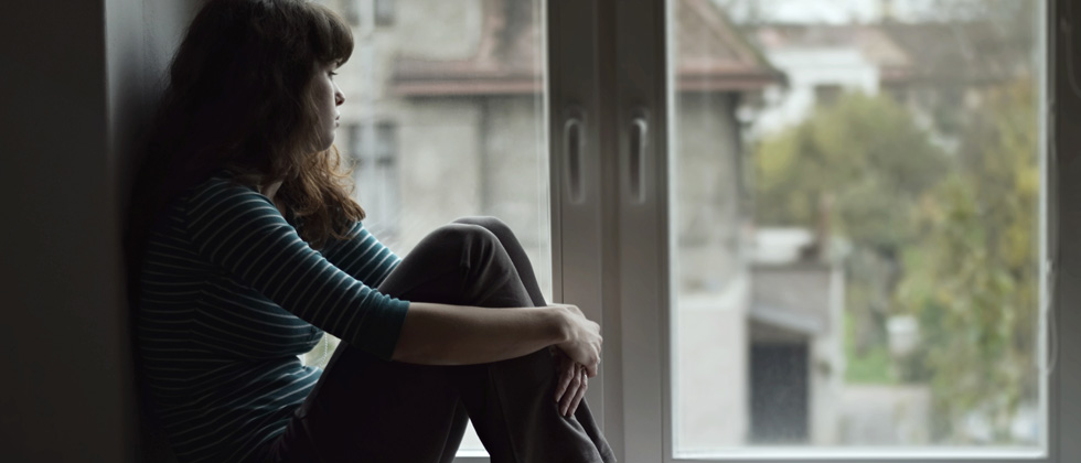 A woman looking upset and sitting on a window ledge staring out