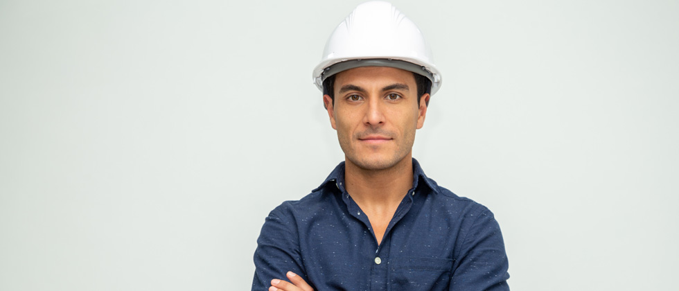 Man wearing a hard hat looking serious into the camera