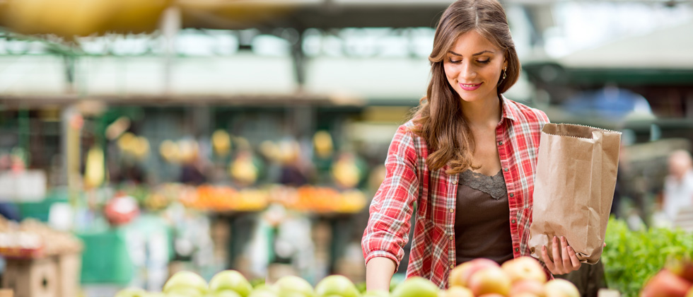 A young woman in the produce aisle picking up groceries