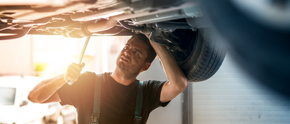 A male mechanic working on a car in a garage