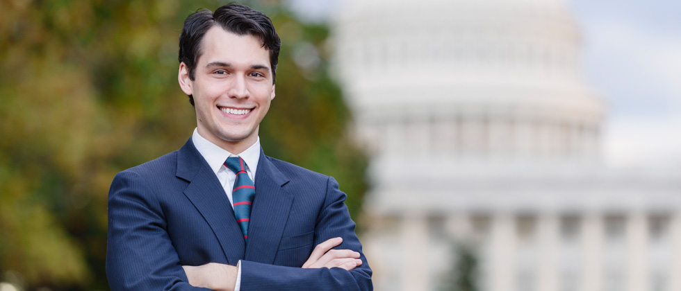 A man dressed in a suit & tie in front of a capital building