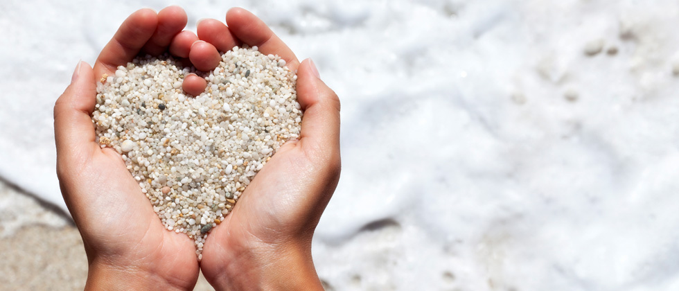 Someone holding sand in their hands making it form a heart
