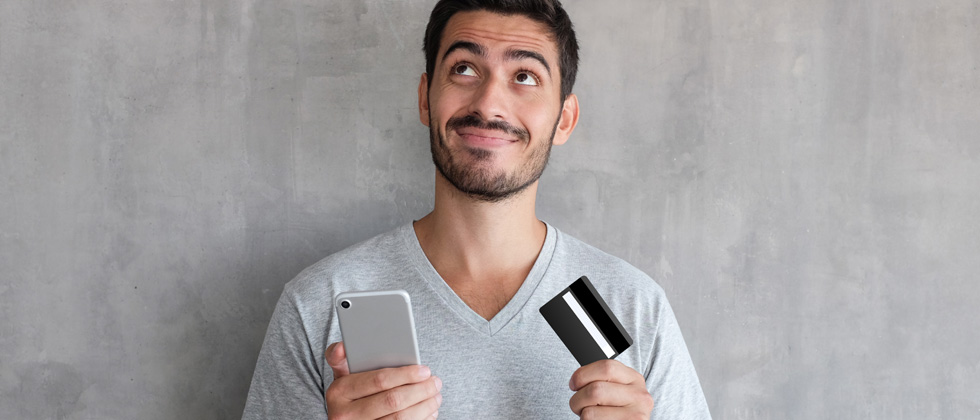 A guy on his phone looking a credit card thinking about buying something