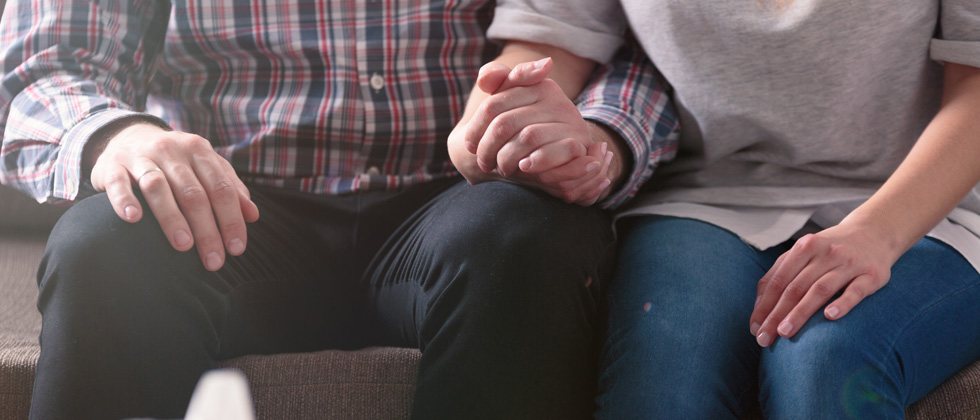 A couple sitting other with their hands held together resting in their lap