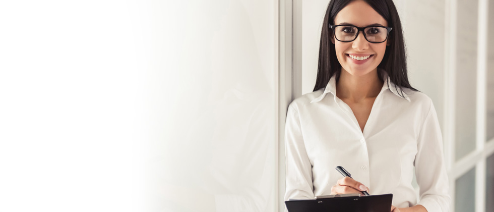 A professional woman smiling with a notepad