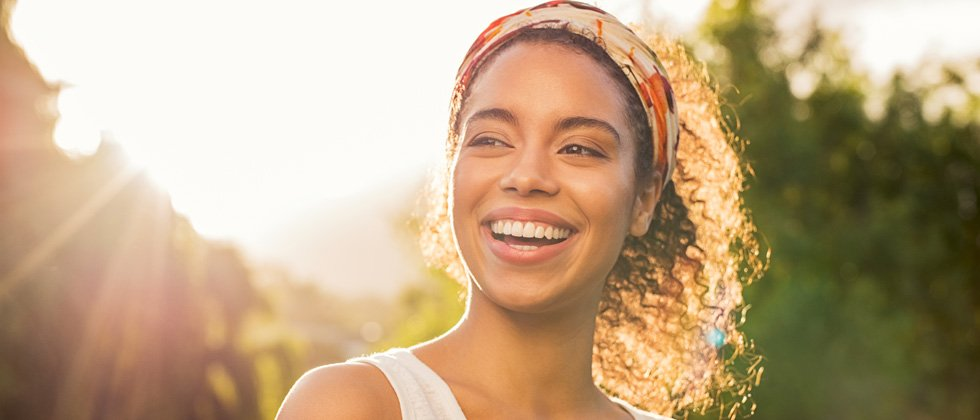 A woman with a huge smile standing under a beaming sun