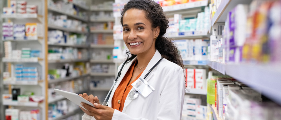 A woman pharmacist standing in a pharmacy looking at a prescription