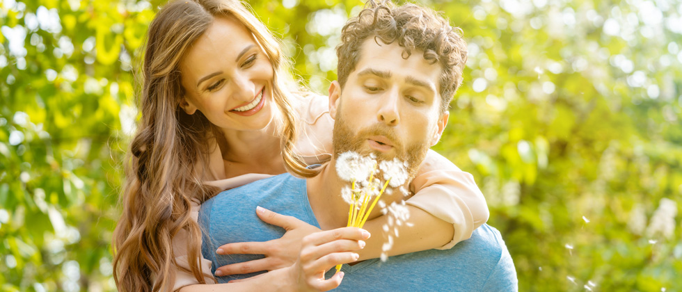 A woman on her date's back holding dandelions while he blows on them