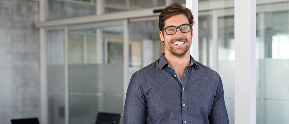Handsome guy wearing glasses standing in a corporate office