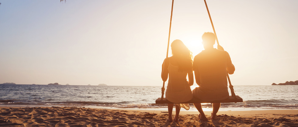 Couple sitting on a swing together on the beach