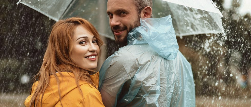 Couple caught in the rain under an umbrella together