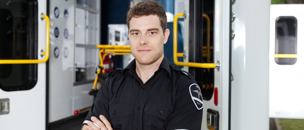 A male paramedic standing in uniform outside an ambulance