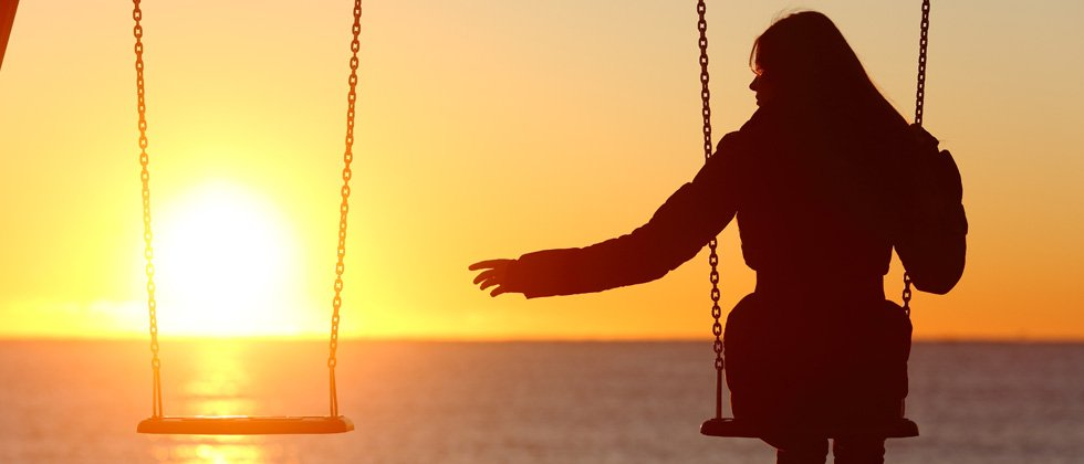 Woman on a swing at sunset reaching for an empty swing next to her