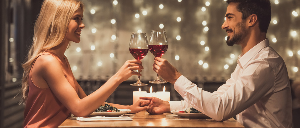 A couple on a date drinking wine and holding hands