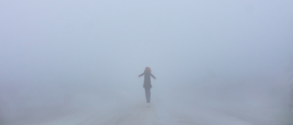 Someone standing at a distance in the middle of a foggy street