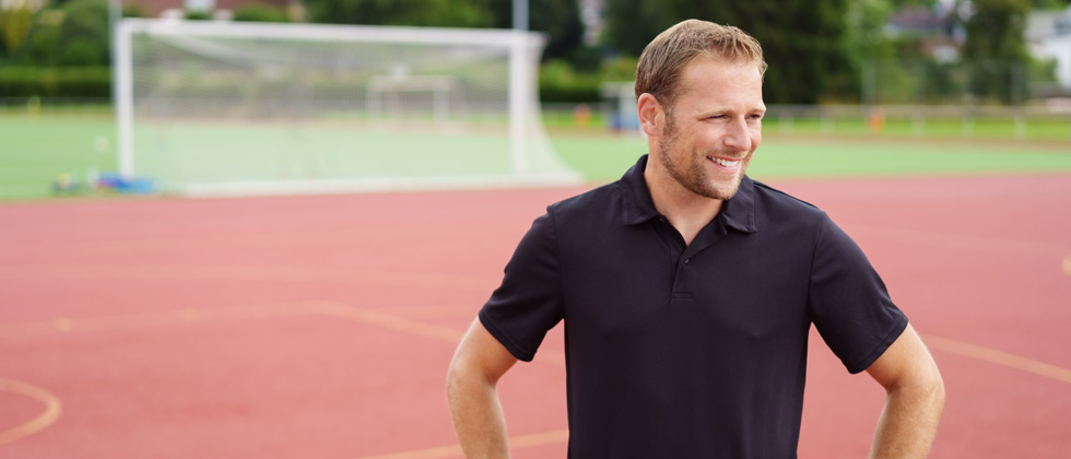 A male coach standing on a track smiling