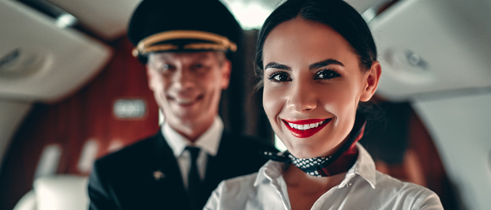 A woman flight attendant standing in a plane cabin with the pilot