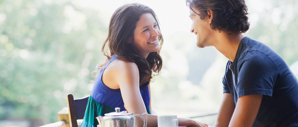 Young couple on a date outside smiling and laughing over coffee