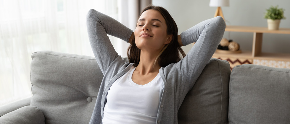A woman sitting on the couch relaxing with her hands behind her head