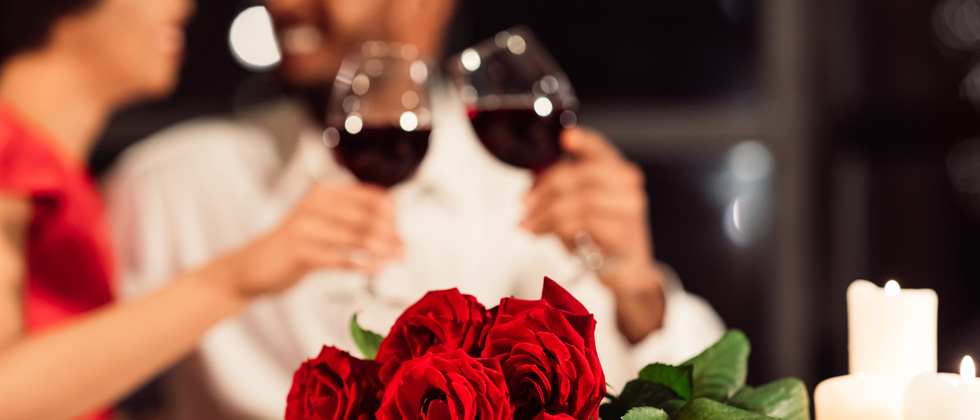 Couple enjoying red wine with a bouquet of roses in front fo them