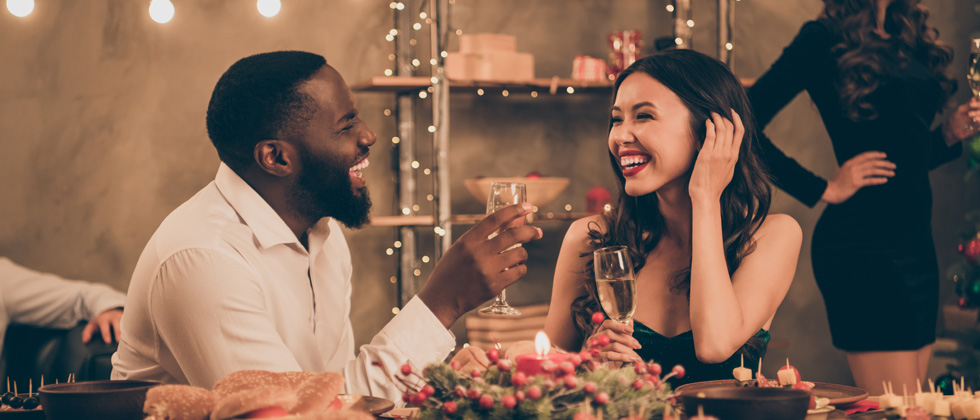 A couple on a date laughing and drinking champagne