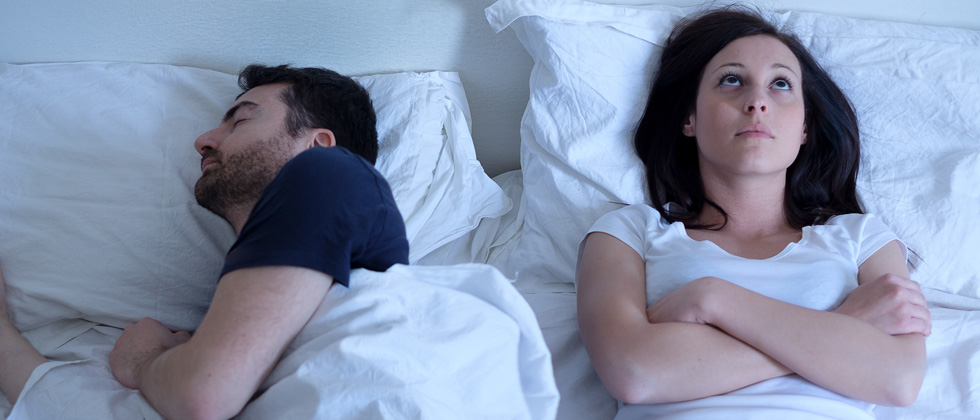 Man sleeping peacefully next to a woman who is awake thinking