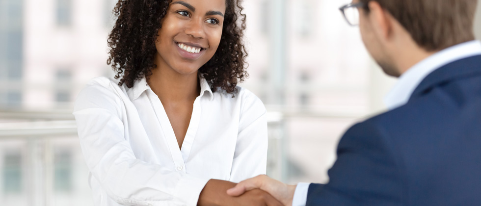 A woman in a business meeting confidently shaking someone's hand